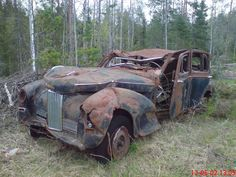 Abandoned old car wreck in the woods, Sweden