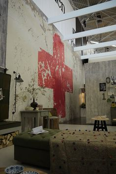 red cross painted on wall, loft, two story ceiling, concrete, metal, vintage pieces . . .