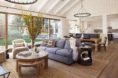 A gray sofa sits atop a natural sisal rug beneath a whitewashed vaulted ceiling in a sunny, California living room.