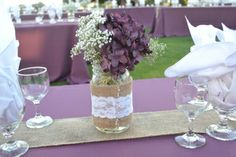 Burlap and lace wedding ideas. Burlap and lace center pieces made with baby's breath and hydrangeas in a mason jar. Burlap, lace, purple, and pearl themed wedding.