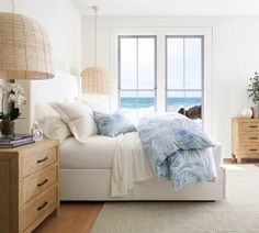 Shop the look of these soothing palmy bedroom. Neutral coastal bedroom with wood furnishings, wicker pendant lights and breezy blue bedding with a palm leaf motif.
