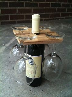 """This handmade wine glass holder sits perfectly on the neck of a wine bottle.  It is perfect for a picnic or small """"get togethers"""". Four wine glasses slide into slots in the corners to hang upside down until they are needed. Racks are 6"""" x 6"""" and of varying thickness.   Made from wood salvaged from New York State.  Wood has been lightly sanded and finished with shellac."""