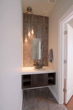 This light fixture for the powder room. A brown textured backsplash adds dimension and visual interest to this modern powder room. The tall ceilings are accentuated by the small rectangular mirror and graduated-height pendant lights.
