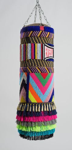 "Jeffrey Gibson : This Is Our House 2014 found vinyl punching bag, glass and plastic beads, artificial sinew, brass and steel studs, wool military blanket, acrylic yarn, steel chain 42"" H X 14"" W X 14""D"