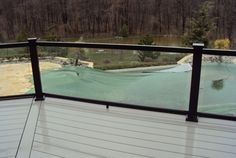 Clad existing concrete porch  steps in grey composite decking. Replace existing railings w/choc brown railings w/glass panels to match deck in backyard.
