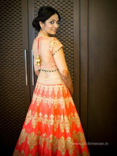 Gorgeous bride in an ombre coral lehenga