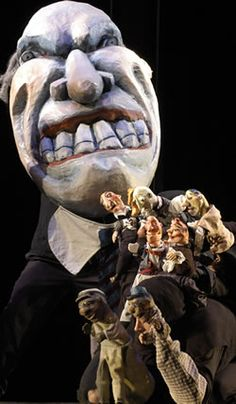 Large-scale puppet with a menacing grin and huge teeth, with smaller puppet figures in front at chest level