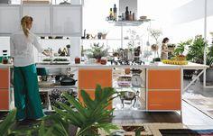 """""""Modulární"""" kuchyň s řadou volných polic využívá na dvířka skříněk kov. Zavěšené skříňky jsou přístupné z obou stran, fungují tak jako příčka."""