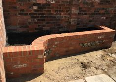 Brick retaining wall with flint panels Brickwork, Firewood, Garden Design, Wall, Home Decor, Woodburning, Masonry Construction, Walls, Backyard Landscape Design