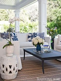 Atop an RH striped rug, sofas from Lane Venture are upholstered in white Sunbrella fabric and accessorized with blue-and-white pillows. Tabl...