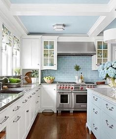 What a lovely kitchen! Loving the dark floors and brick splashback!. 💙 the light pastel color palette + Mixing blue and white radiates classic cottage style😍. (Source:Better homes and gardens). #kitchen #kitchendesign #kitchenisland #kitchendecor #kitchenideas #kitcheninspo #kitchencabinets #pastelkitchen #babyblue #hardwoodfloors #whitecabinets #countrykitchen #classickitchen #countryliving #coastalliving #housedesign #homeliving #houseandhome