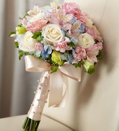Gorgeous cream roses, pink mini carnations, pink Peruvian Lilies, pink double lisianthus, blue hydrangea and bupleurum are brought together to create an unforgettable bouquet. Tied together with a soft peach satin ribbon accented with pixie pearl pins