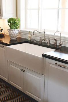 Beautiful kitchen remodel with white kitchen cabinets, farmhouse sink, black honed beveled granite counter tops, subway tiles backsplash, brushed nickel faucets and herringbone rug.