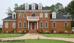 Большой красивый дом из красного кирпича с серой кровлей.