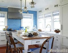 Seaside Kitchen  A nautical theme runs throughout this small kitchen with industrial pendant fixtures, a blue-and-white color theme, and organization that's shipshape.