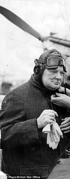 Winston Churchill having his flying helmet removed after arriving at 615 Squadron at Royal Air Force Kenley.   WWII