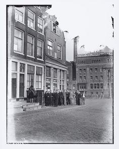 Groep mannen voor café 'De Gouden Reaal', met op de achtergrond de Stoommeelfabriek Holland. Oktober 1947.