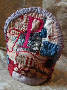 This tea cosy was made specifically for a teapot.  .... made of antique French silks and cotton, wool, linen, cotton, felt, with hand embroidery by Tara Badcogk