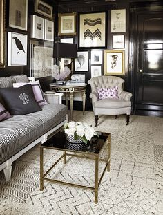 """Art hung """"salon wall"""" style on a black lacquer wall is rich and dramatic.  The gold, black, grey, and ivory is an elegant combination for this living room or sitting area."""