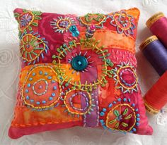 This little beauty is pure, saturated fun! Bright batik cottons are pieced together in a fun patchwork design. Rich raspberry, sunlit orange, and candy apple red are just a few of the colors of fabric used. Fun circles pop with hand embroidery in brilliant perle cotton thread. You will find lime green, brilliant blue, grape, green and cobalt knots and stitches by the hundreds. Two bright buttons and two coordinating pins bring it all home. This is such a fun and happy pincushion, I am sure…