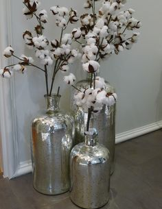 Peacock Alley filled three sizes of cypriot jars with cotton branches. It softens the wall and makes the space feel like balls of snow. Featured in the 2016 Home for the Holidays Designer Showhouse in Atlanta.