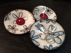 Disk pendants with hand drawn flowers.