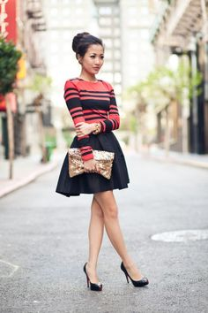 stripe red long sleeve top with pleated skirt and black stilettos topped with a ballerina bun