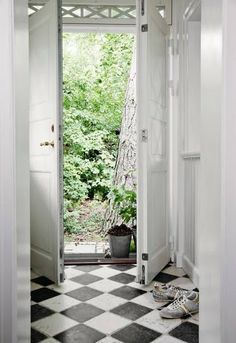 Light-filled entry with double doors, transom windows & diamond pattern floor