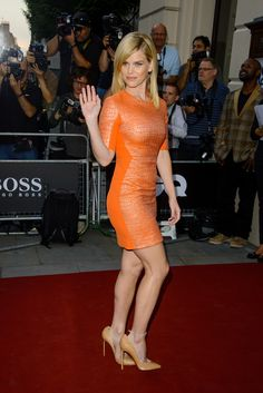 Alice Eve gorgeous legs in a curve hugging orange mini dress and pumps