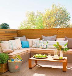 Terraza pequeña con madera, sofá rinconero con cojines, alfombra de fibras, mesa de centro y capazo