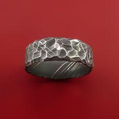 This 7mm wide DAMASCUS STEEL ring has a ACID FINISH and a Rock Hammered Texture. Each ring is custom made and the pattern unique, so no two rings are exactly alike. Damascus Steel rings are very desirable. Your ring comes with a COMFORT-FIT for extra satisfaction. Our DAMASCUS ring WILL NOT RUST OR TARNISH.Damascus steel is an ancient art form. This blacksmith alloy is made using two types of Surgical and Fine Stainless steel that are layered in 100 alternating layer and then worked. It is…