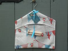 Gorgeous oilcloth peg bag in pretty Union Jack bunting print, complete with dolly pegs. From www.etsy.com/shop/dagenaisdesign