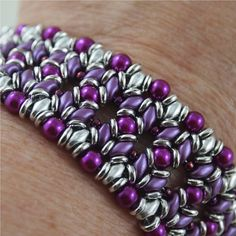 This slinky and luxurious bracelet has been hand bead woven using purple and silver Super Duo beads, magenta pearls and seed beads and silver