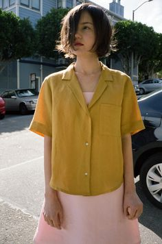 Light linen, mustard yellow, boxy cut, button down - this shirt has so many things going for it. Wear on sunny days, or on days where you wish there was more sun. Featuring a single breast pocket and a blazer-esque collar, this piece would look great buttoned up, or unbuttoned over a simple ta