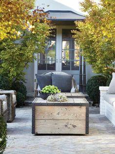 terrasse avec salon de jardin et table-coffre entouré d'érables
