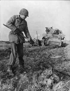 An American sapper uses a mine detector near the corpse of a German KIA to check for booby traps. Although the latter practice was not used by the Germans as extensively as by the Japanese, booby traps near KIAs were not unknown in Europe