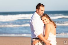 A loving bride and groom share a hug on a deserted beach