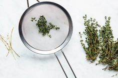 The easiest way to remove thyme leaves from the stalk: a fine-mesh strainer. Simply push the end of the thyme stem through a hole and carefully but forcefully pull the stem through. The leaves will be collected in the strainer, ready to use whole or be chopped.