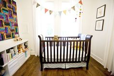 light and airy nursery space. love the quilt hanging on the wall as a piece of art.