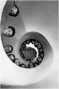 looking upward at spiral staircase with childrens faces looking down