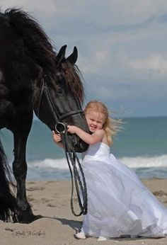 A little girl and a horse by the ocean