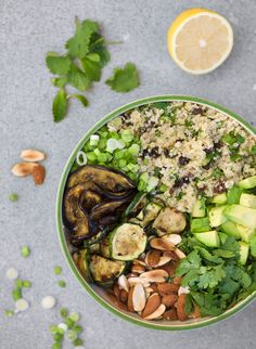 moroccan quinoa salad. 1 zucchini - cut in thin slices,1 eggplant -cut in thin slices, olive oil, 1 clove garlic - minced, salt, 1 1/2 cup quinoa,1 tbsp cinnamon, 1 lemon, 2 bunches mint leaves, 1 bunch cilantro/coriander, 3 tbsp raisins, 2 avocados - cut into 1 inch squares, 4 small spring onions, chopped 1 cup almonds -divided in half, roasted and salted.