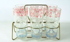 Mid Century Modern retro-fabulous Swanky Swig ice tea drinking glasses circa 1950s.  These pink, blue and white glasses have a kitchen motif and would be great for lemonade, iced tea or as highball glasses.  Add a touch of the 50s to your kitchen or barware.  All the glasses are in very good condition with minimal wear to the pattern (no chips/breaks/cracks).  The wire gold-tone carrier shows signs of wear but is sturdy and hold the glasses well. The set in the carrier measures approximately…