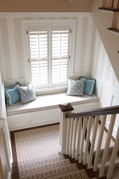 Window seat, panelling, striped walls, shutters, wood stairs with white balusters and runner - love it all.
