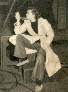 Actin' naturally, in wide-legged Bryn Mawr jeans and a belted trench coat, on the set of MORNING GLORY (1933).
