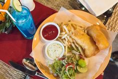 Fish and chips with a blue cocktail. This delicious food can be found at the Grand Mirage Resort in Nusa Dua, Bali. Great family travel vacation. #Bali #delicious #food