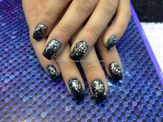 Acrylic nails with black gel polish and silver glitter