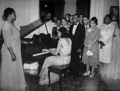 A young African-American woman playing the piano for a captive audience. Photograph by George Strock. Missouri, USA, 1940.
