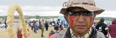 """Jon Don Ilone Reed, an Army veteran and member of South Dakota's Cheyenne River Sioux Tribe, poses for a photo at an oil pipeline protest near the Standing Rock Sioux reservation in southern North Dakota on Thursday, Aug. 25, 2016. Reed said he fought in Iraq and is now fighting """"fighting for our children and our water."""""""