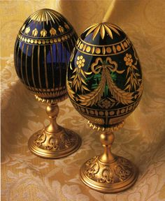 (2)__FABERGE eggs__Enameled Easter and Winter Palace Crystal Egg . Mouth blown and copper wheel engraved crystal egg with 24k hand-painted gold decoration. Mounted on gold-plated bronze Laurel stand.
